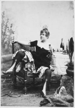 La Goulue assise sur une chaise, jambes ÈcartÈes, tenant une cigarette à la main droite et un verre de vin la main gauche. Vers 1885